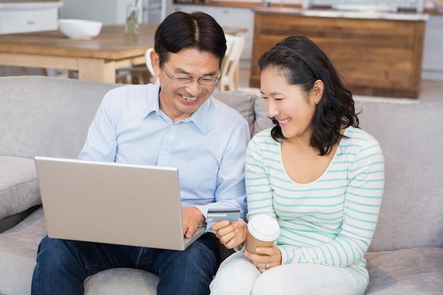 Gelukkig paar dat online op de bank winkelt