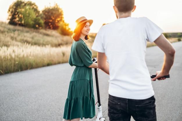 Gelukkig paar dat op autopedden loopt. een jonge vrouw in jurk en hoed op zonsondergang. op de voorgrond keert een man de lens de rug toe