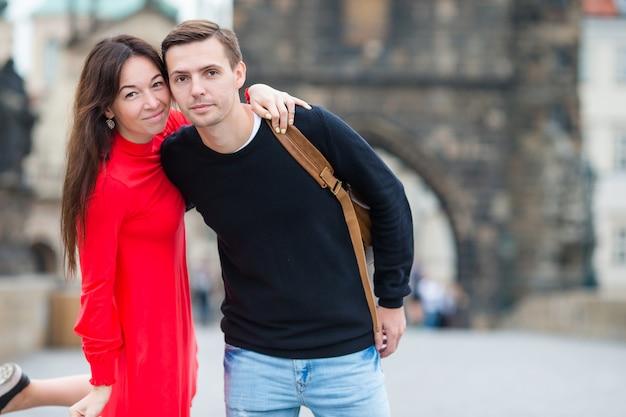 Gelukkig paar dat op charles bridge in praag loopt. glimlachende liefhebbers genieten van stadsgezicht met beroemde bezienswaardigheden.