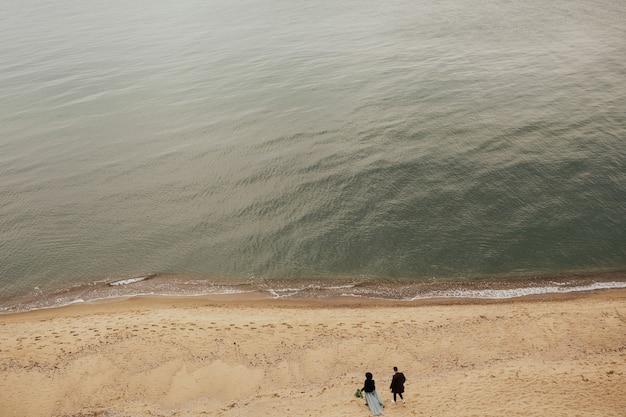 Gelukkig paar dat op het strand aan de zwarte zee loopt.