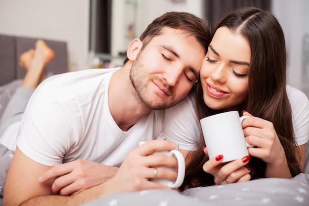 Gelukkig paar dat pret in bed heeft. intiem sensueel jong koppel in slaapkamer genieten van elkaar