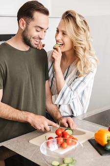 Gelukkig paar dat samen kookt terwijl ze in de keuken staan, groenten hakken aan boord, omarmen