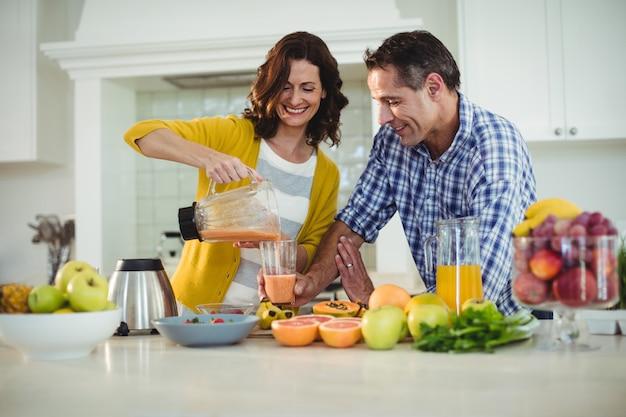 Gelukkig paar dat smoothie in keuken voorbereidt