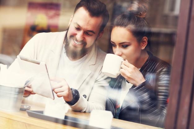 Gelukkig paar dat tablet in restaurant gebruikt
