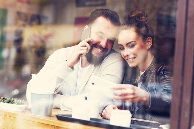 Gelukkig paar dat telefoons in restaurant gebruikt
