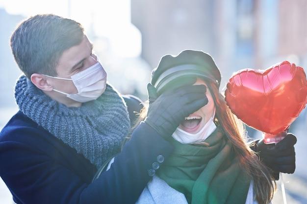 Gelukkig paar dat valentijnsdag in maskers viert tijdens de covid-19-pandemie in de stad