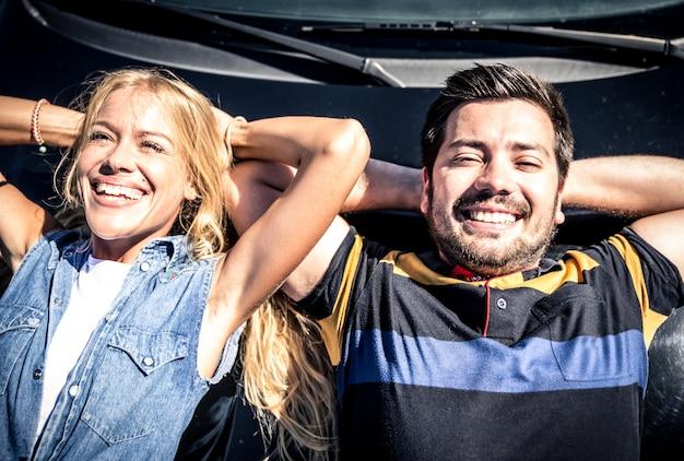Gelukkig paar dat van zon op de autokap geniet