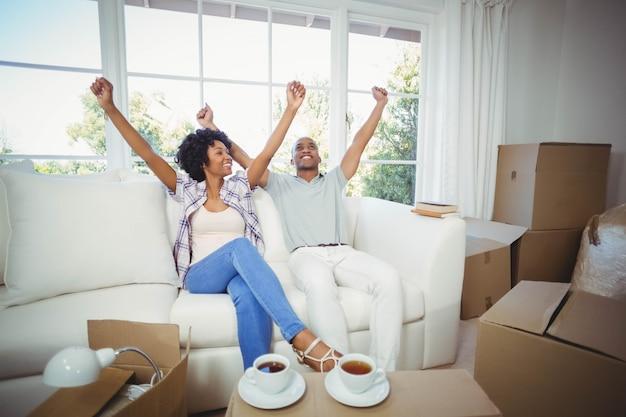 Gelukkig paar dat vuisten in hun nieuw huis opheft