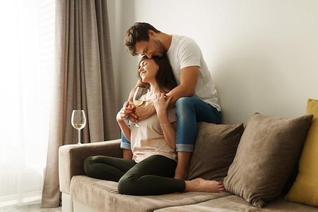 Gelukkig paar dat wijn drinkt en thuis ontspant