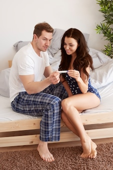 Gelukkig paar dat zwangerschapstest bekijkt