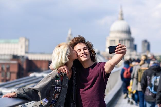Gelukkig paar die een selfiefoto op de millenniumbrug van londen nemen