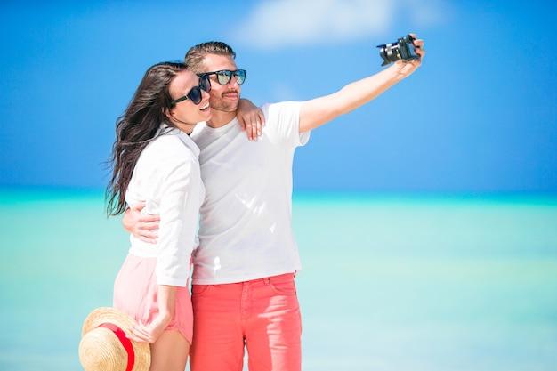 Gelukkig paar die een selfiefoto op wit strand nemen