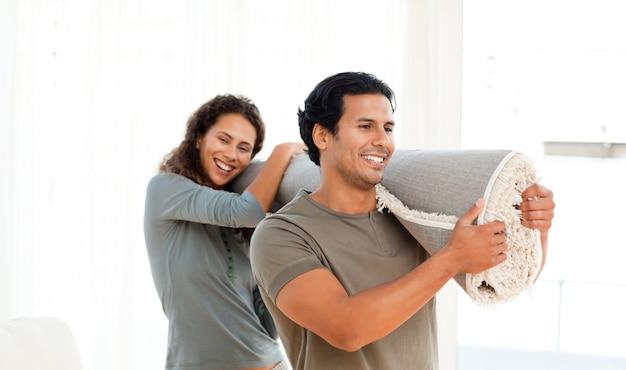 Gelukkig paar die een tapijt samen in hun nieuwe woonkamer houden