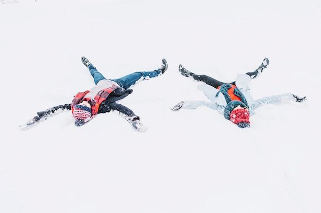 Gelukkig paar die engelen in sneeuw maken