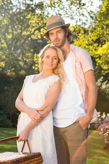 Gelukkig paar die met een picknickmand omhelzen in de tuin