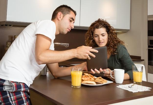 Gelukkig paar die tablet thuis kijken ontbijt