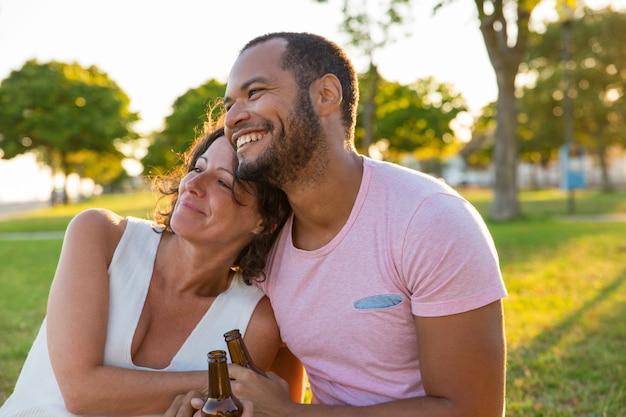 Gelukkig paar die van openluchtdatum genieten bij zonsondergang