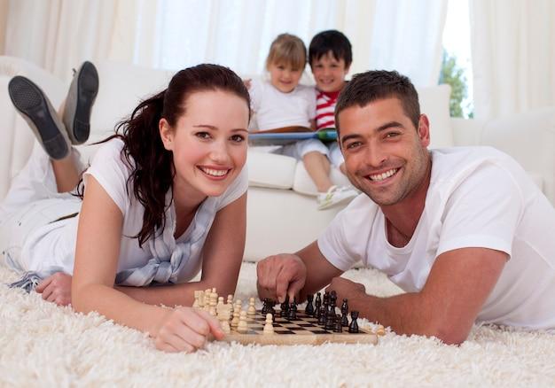 Gelukkig paar het spelen schaak op vloer in woonkamer