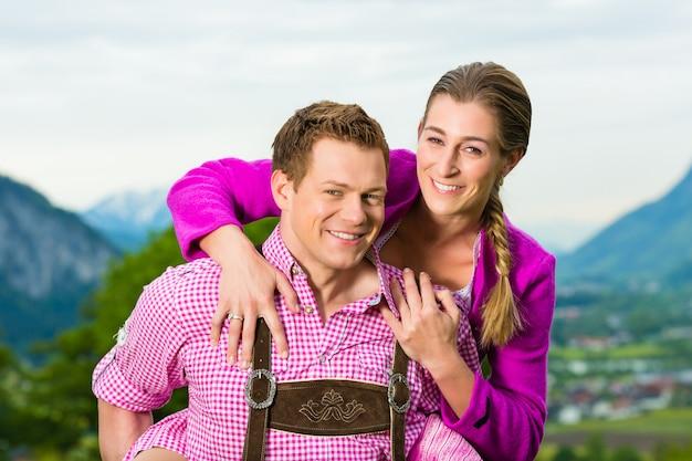 Gelukkig paar in alpiene weide in tracht
