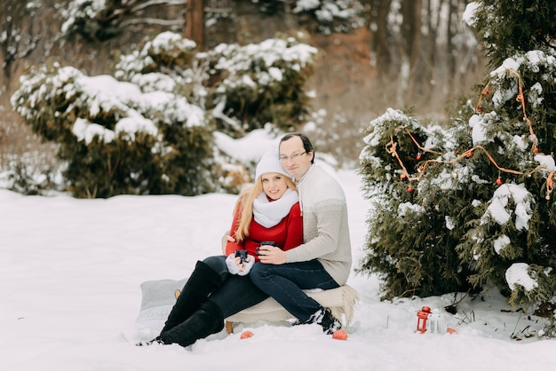 Gelukkig paar in de winter het drinken van thee en zittend op een slee