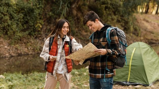 Gelukkig paar in het bos die samen op het vooraanzicht van de kaart kijken