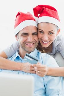Gelukkig paar in santahoeden die online winkelen