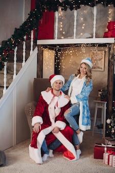 Gelukkig paar in sneeuwmeisje en santa claus-kostuums