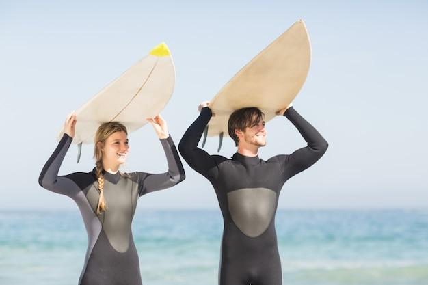 Gelukkig paar in wetsuit dragende surfplank lucht