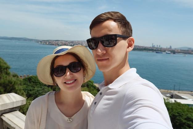 Gelukkig paar in zonnebril staat op de heuvel en poseert zoenen tegen een prachtig landschap van extreem dichtbij zicht