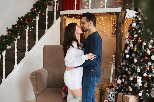 Gelukkig paar jonge geliefden knuffelen terwijl ze poseren in de buurt van de kerstboom in de woonkamer