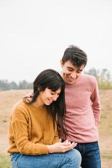 Gelukkig paar kijken naar mobiel en lachen