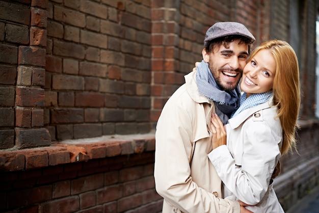 Gelukkig paar knuffelen elkaar op straat