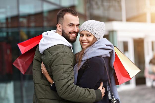 Gelukkig paar met boodschappentassen na het winkelen in de stad glimlachen en knuffelen