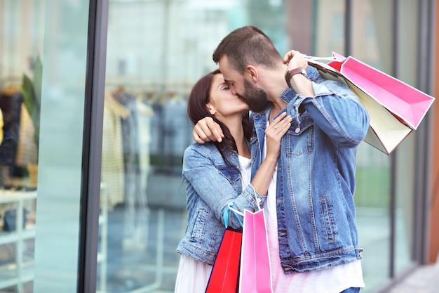 Gelukkig paar met boodschappentassen na het winkelen in de stad
