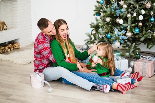Gelukkig paar met dochter naast kerstboom