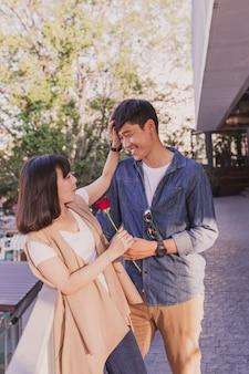 Gelukkig paar met een roos op een balustrade leunt