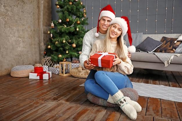 Gelukkig paar met kerstcadeau thuis