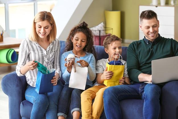 Gelukkig paar met kleine geadopteerde kinderen na thuis winkelen