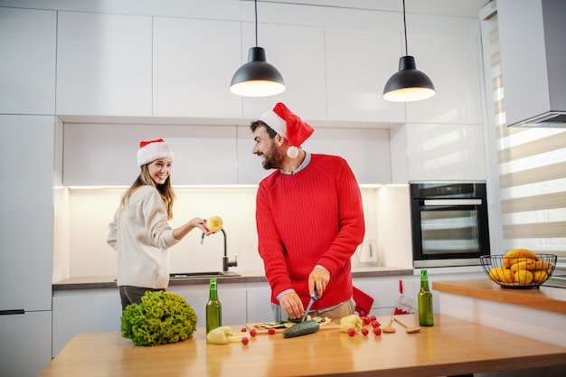 Gelukkig paar met santahoeden op hoofden die gezond voedsel voorbereiden op oudejaarsavond