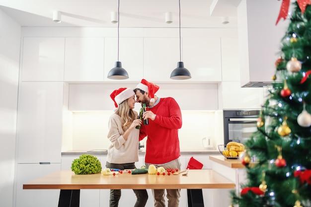 Gelukkig paar met santahoeden op hoofden die met bier roosteren terwijl status in keuken op kerstmisvooravond