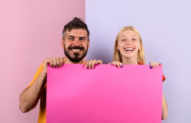 Gelukkig paar met uithangbord glimlachend paar dat groot leeg bord presenteert gelukkige familie houdt