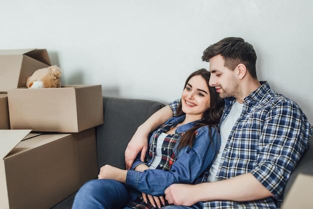 Gelukkig paar ontspannen op de bank met plezier op de verhuisdag, opgewonden jonge huiseigenaren genieten van verhuizing naar een nieuw huis