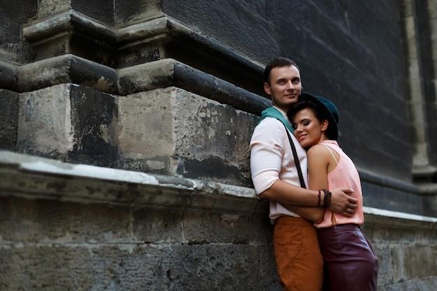 Gelukkig paar op een stadsstraat. jonge vrouw in een hoed en een lederen rok en een zachte man knuffelen op straat. liefde en liefdesverhaal