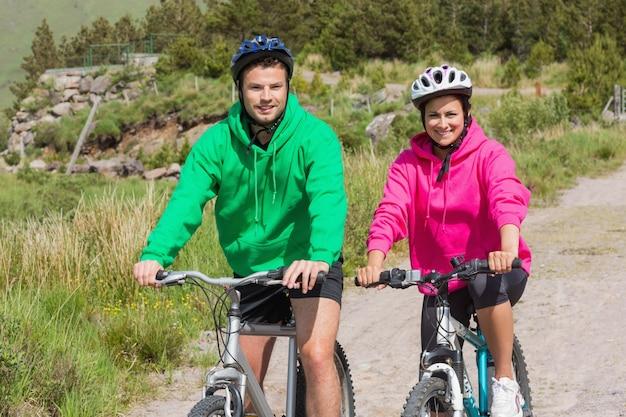 Gelukkig paar op fietstocht dragen hooded jumpers