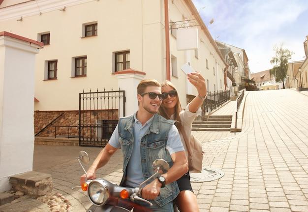 Gelukkig paar op scooter selfie foto maken op smartphone buitenshuis