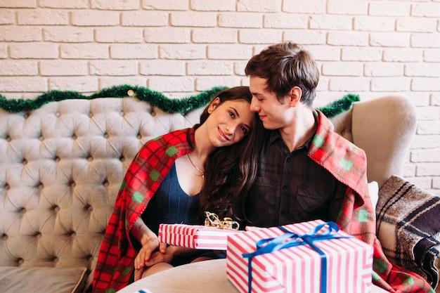 Gelukkig paar rust in de buurt van kerstcadeaus.