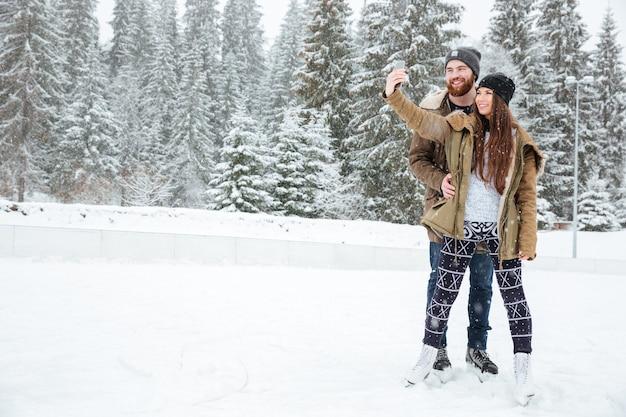 Gelukkig paar selfie foto maken op smartphone buitenshuis