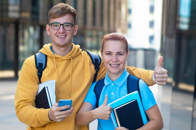 Gelukkig paar studenten. jongen en meisje met boeken die duim tonen
