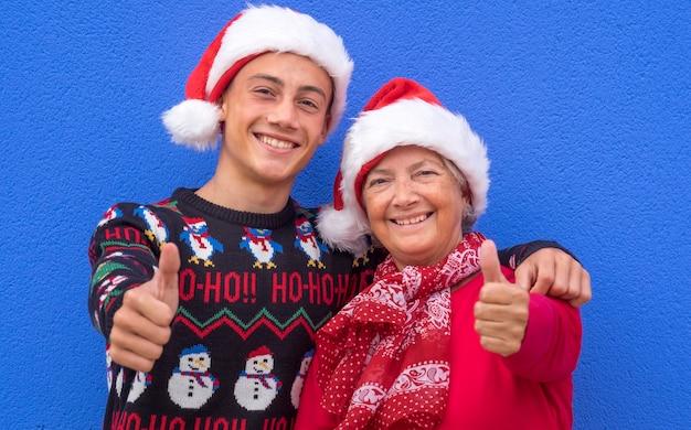 Gelukkig paar tiener kleinzoon met grootmoeder die kerstmutsen en kersttrui draagt en een positief ok teken doet met handen, familie en liefde concept