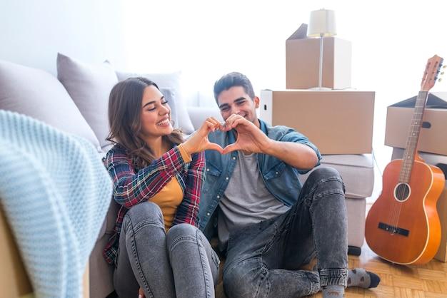 Gelukkig paar tijdens het bewegen van huis dat hartteken toont